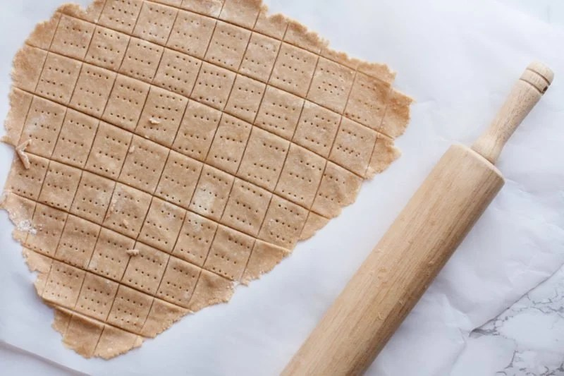 A rolling pin sits near formed cracker dough.