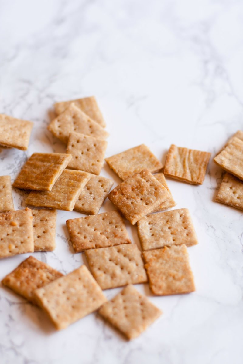 Whole wheat crackers sit scattered on a marbled background