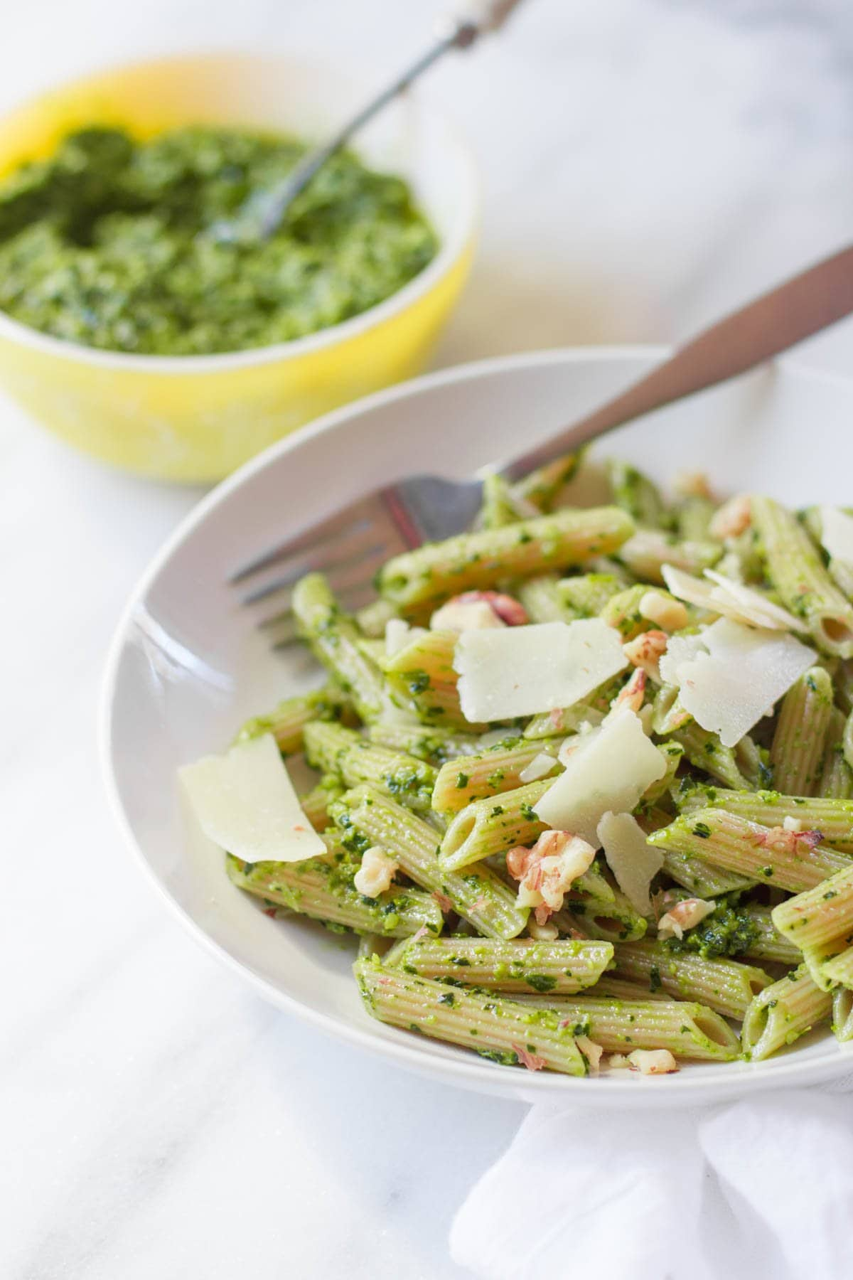 A bowl of pasta sits covered in the pesto and topped with parmesan shavings. A bowl of pesto sits in the distance.