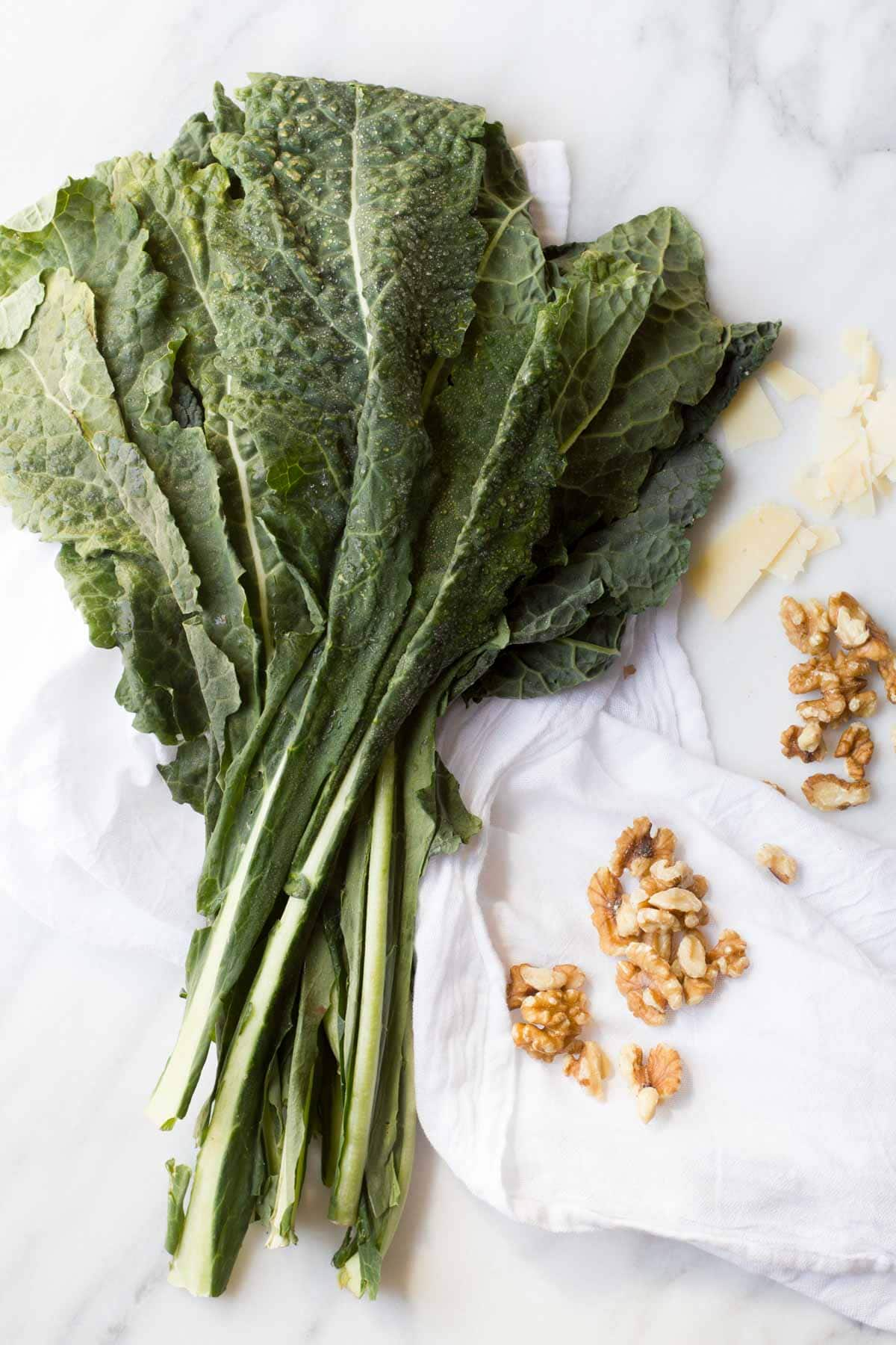 Washed kale and chopped nuts sit together on a white background.