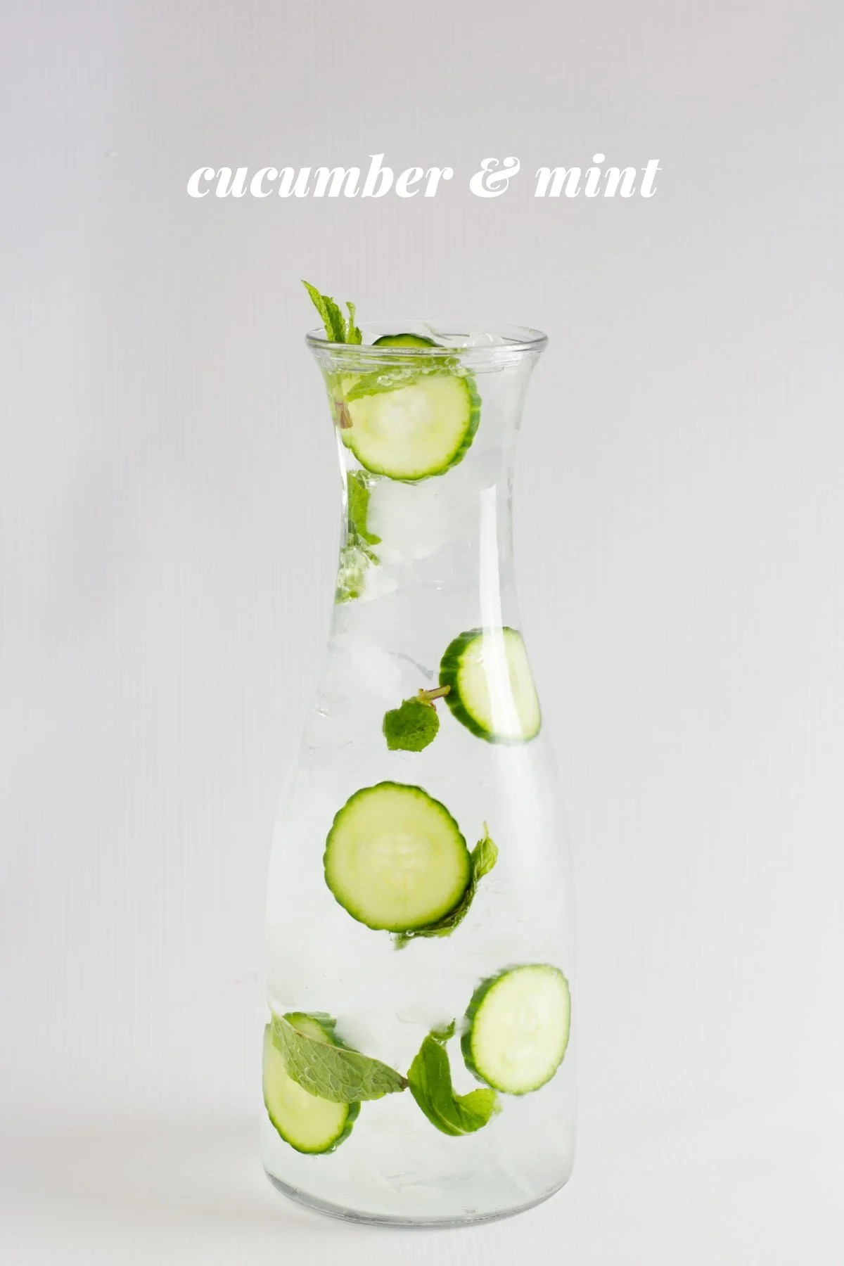 "Cucumber and mint infused water is displayed in a glass carafe. A text overlay reads, ""Cucumber & Mint."""