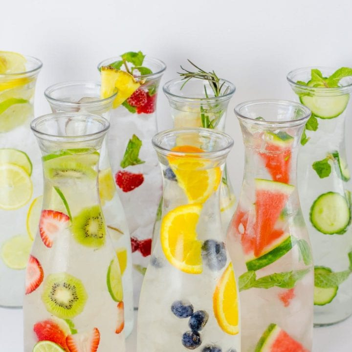 Eight glass carafes filled with different flavors of fruit-infused water are clustered together.