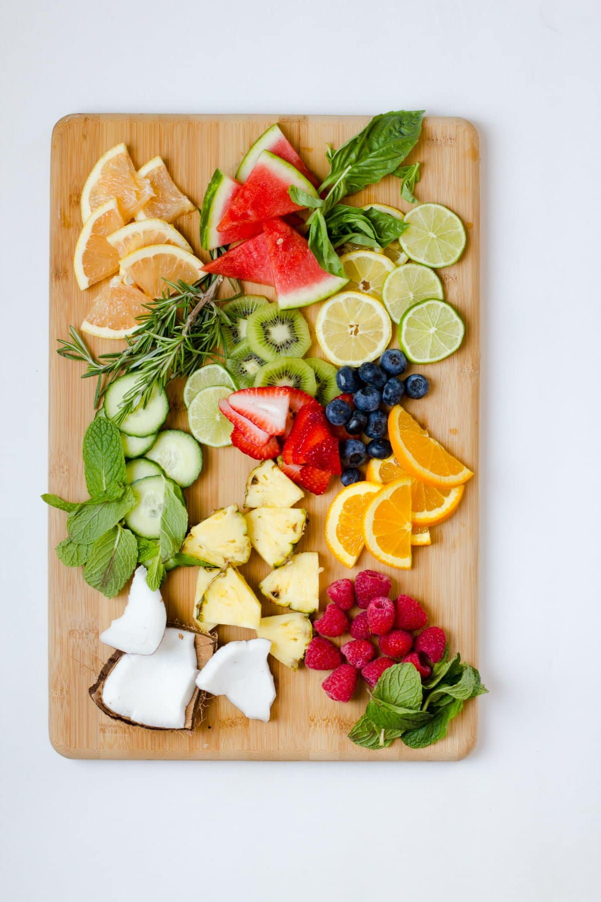 Overhead of a wide variety of sliced fruits and herbs arranged on a wooden cutting board.