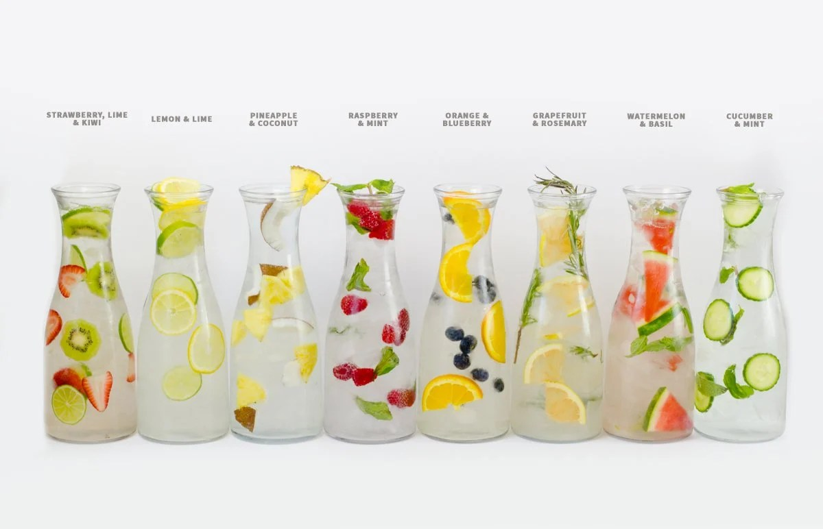 Eight glass carafes of infused water are lined up side-by-side with text above detailing the flavors inside.