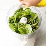 Hand pours olive oil into a food processor filled with fresh basil leaves.