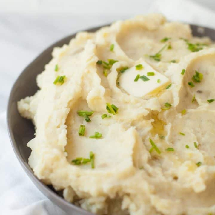Tight view of bowl of fluffy slow cooker mashed potatoes on white countertop. Mashed potatoes are topped with fresh chives and a melting butter pat.