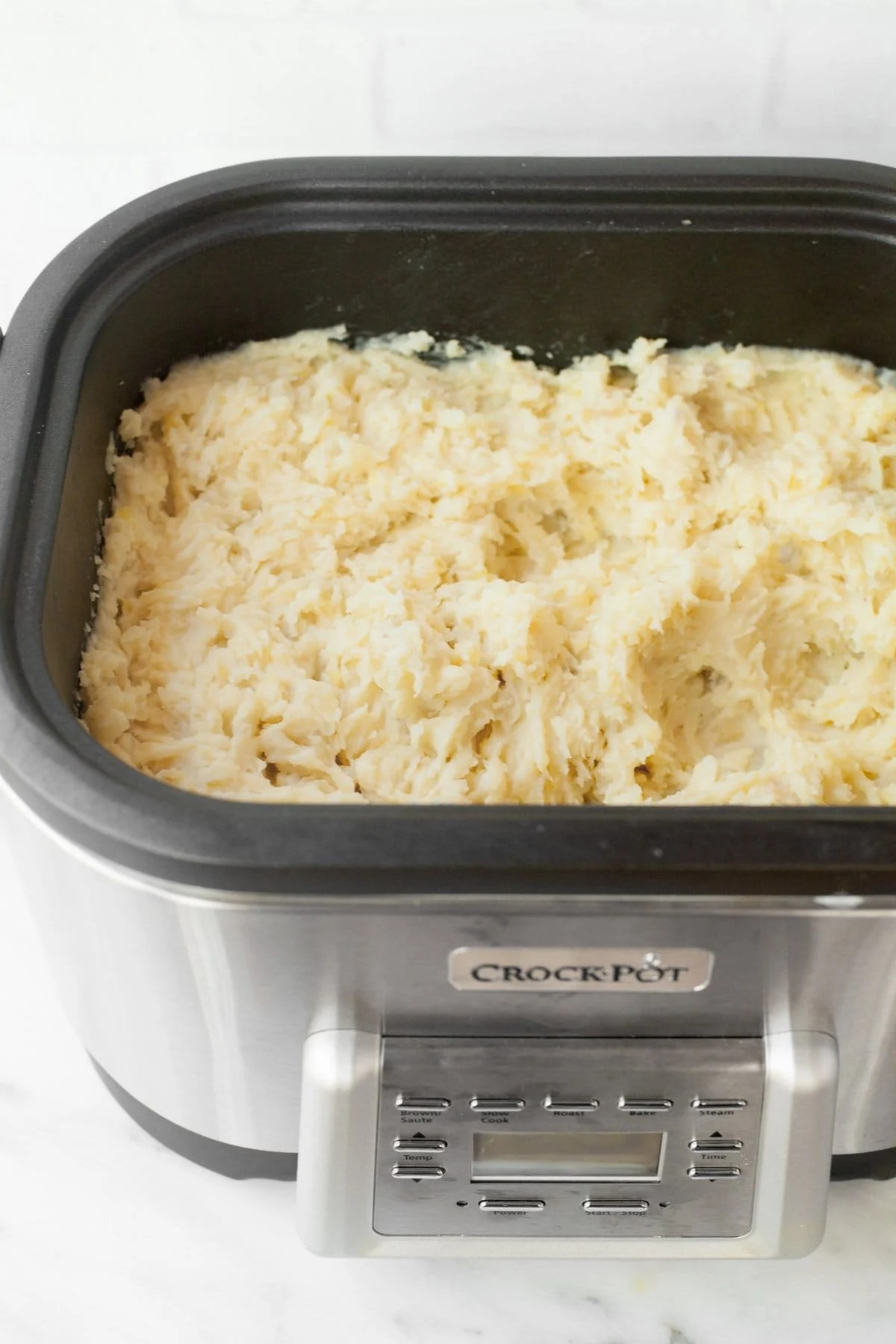 Fluffy mashed potatoes in a large Crock-Pot slow cooker on a white countertop.