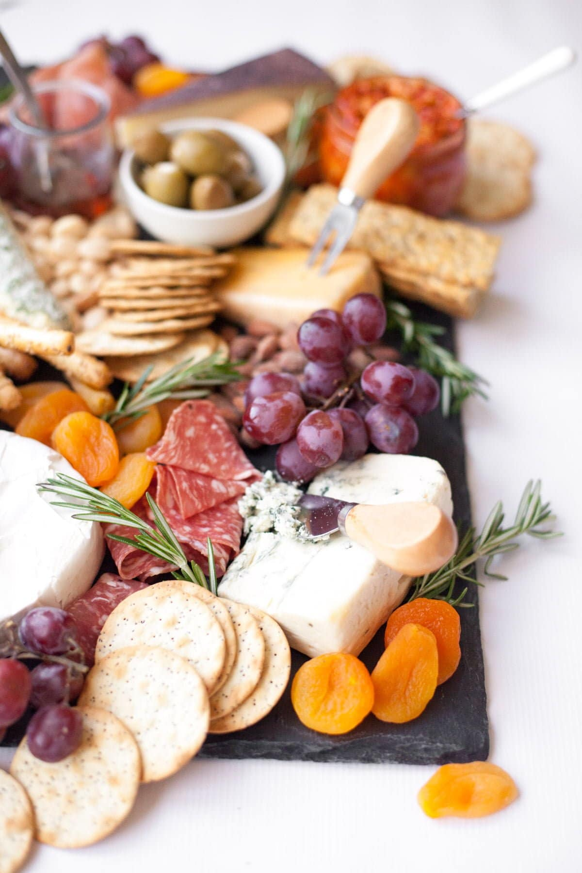 Close up of a cheese board arranged on a slate platter, with various cheeses and crackers, grapes, dried apricots, fresh rosemary, and charcuterie.