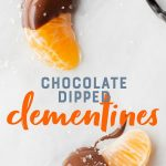 "Two slices of clementine half-covered in chocolate on a white background. A text overlay reads ""Chocolate Dipped Clementines."""