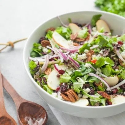 A green salad topped with dried cranberries, toasted pecans, and apple slices sits in a white serving bowl with two wooden serving spoons beside it.