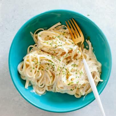 Turquoise bowl of fettucine noodles in a vegan cashew alfredo sauce.