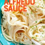 """Noodles with vegan alfredo sauce twirled around a fork. A text overlay reads """"Vegan Alfredo Sauce."""""""