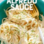 """Turquoise bowl of fettucine noodles in a vegan cashew alfredo sauce. A text overlay reads """"Dairy-Free Alfredo Sauce."""""""