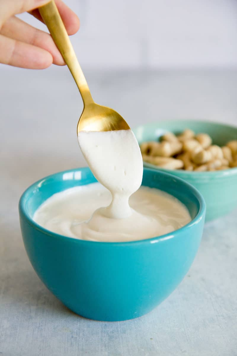 Spoon drizzling cashew cream into a turquoise bowl full of more cashew cream.