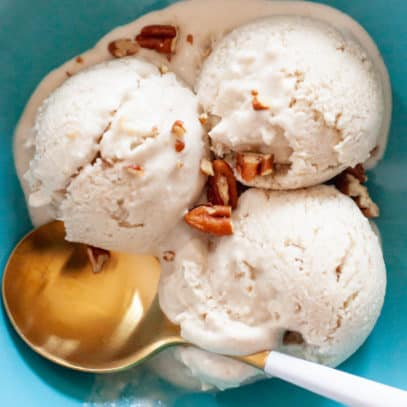 A gold spoon sits in a turquoise bowl with 3 scoops of vegan ice cream.
