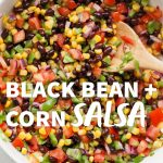 "A white bowl filled with black bean and corn salsa, with a wooden spoon. A text overlay reads ""Black Bean + Corn Salsa."""