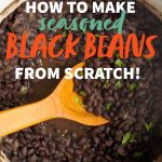 "A pot full of seasoned black beans with a wooden spoon. A text overlay reads ""How to make seasoned black beans from scratch!"""