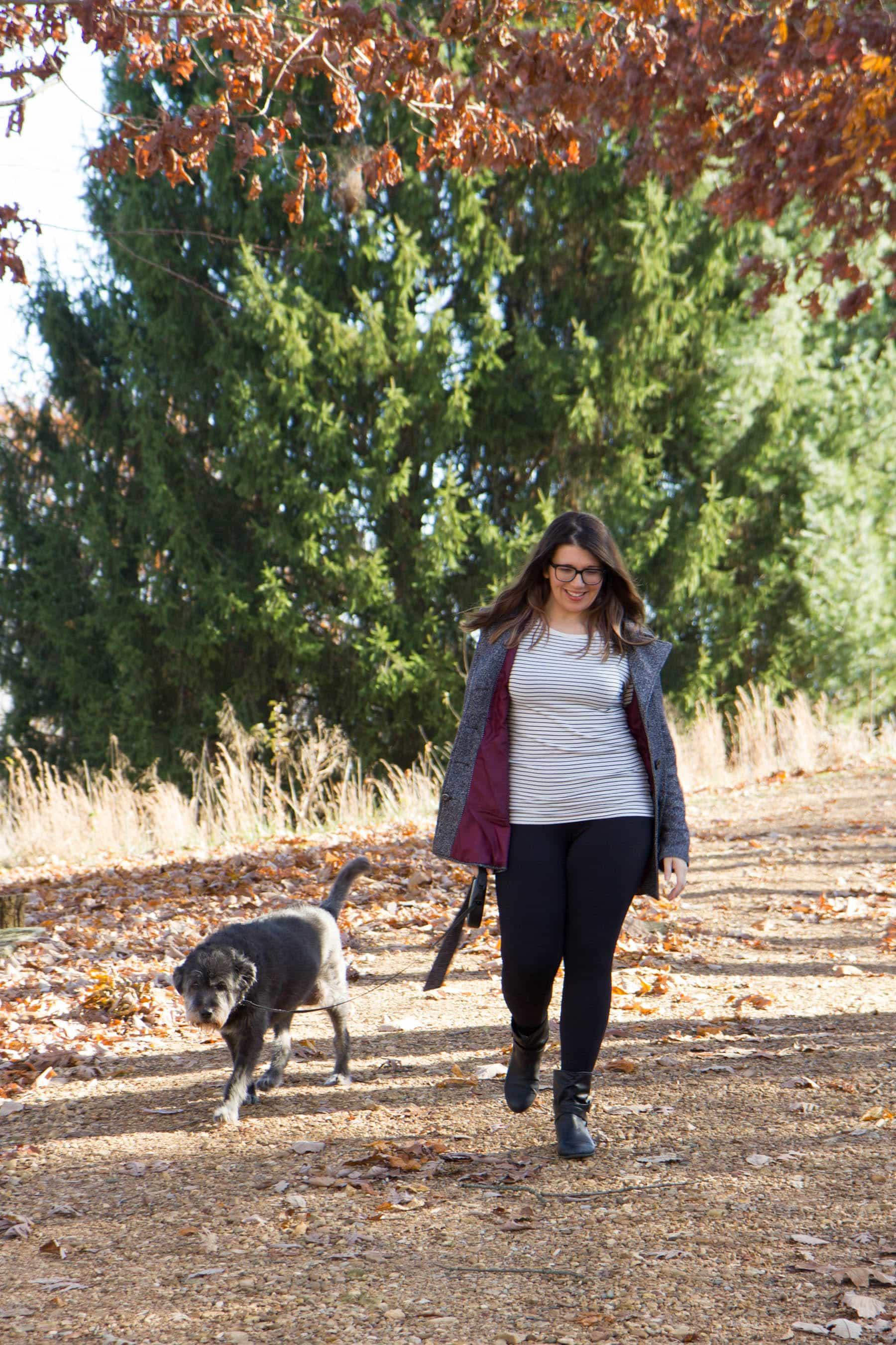 Brunette woman wearing layers walks a grey dog outside.