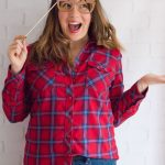 Happy woman with red plaid shirt with 2018 glasses over her eyes