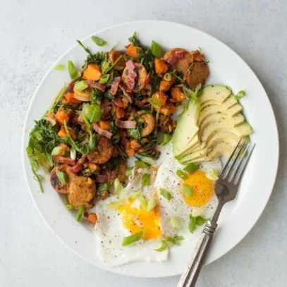 Overhead view of white plate with sweet potato hash, sunny side up eggs, and avocado slices