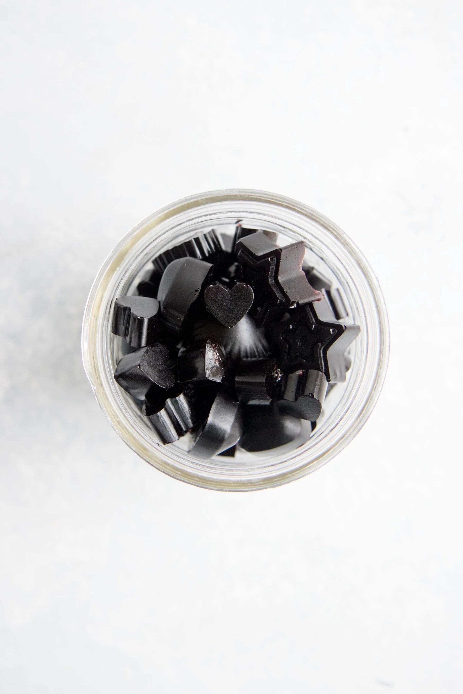 Dark purple gummies sit in a glass mason jar.