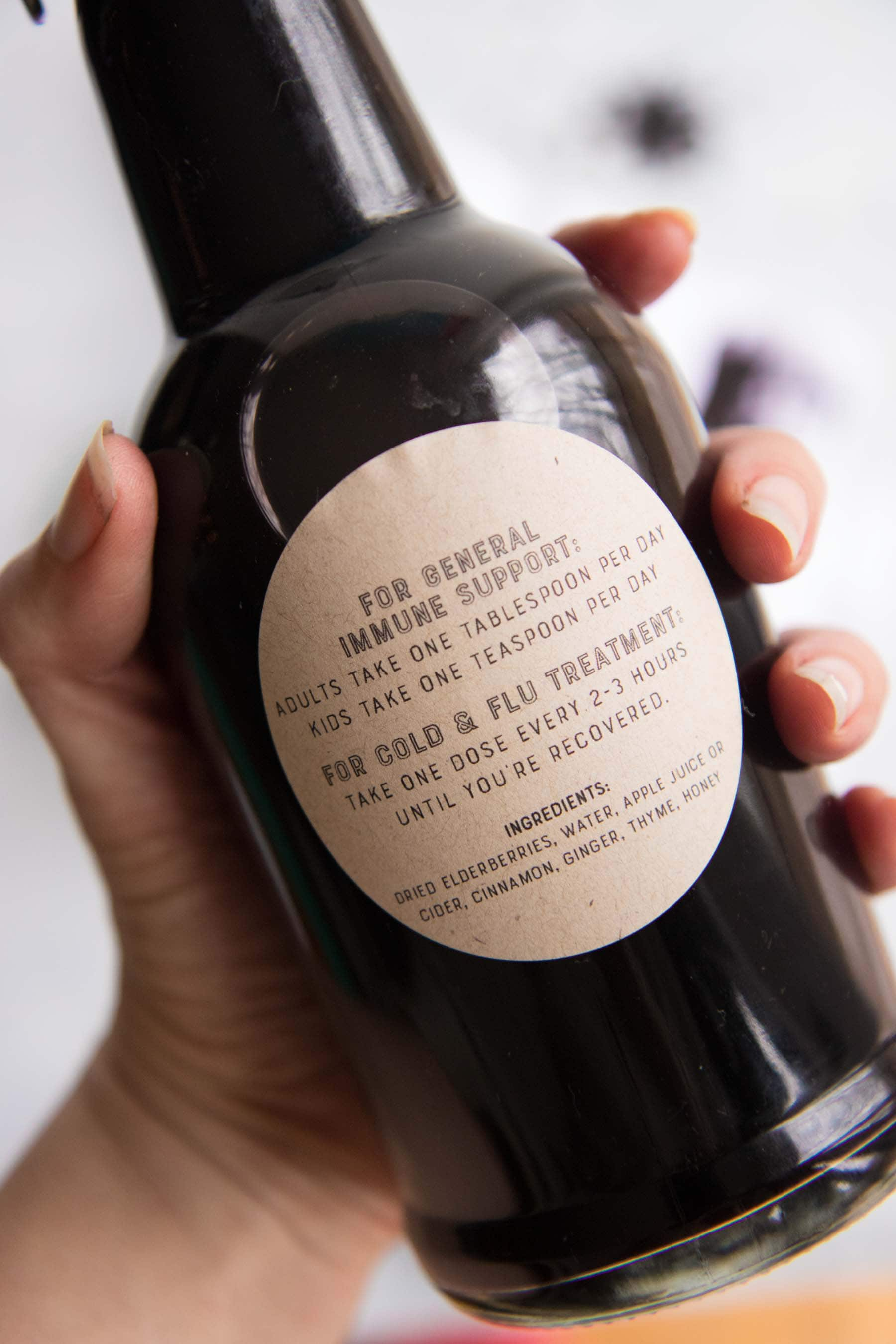 A hand holds a bottle filled with dark purple syrup, showing a label with dosing instructions.