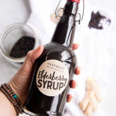 "A hand holds a swing-top bottle labeled ""elderberry syrup"" over a white dish towel and extra ingredients."