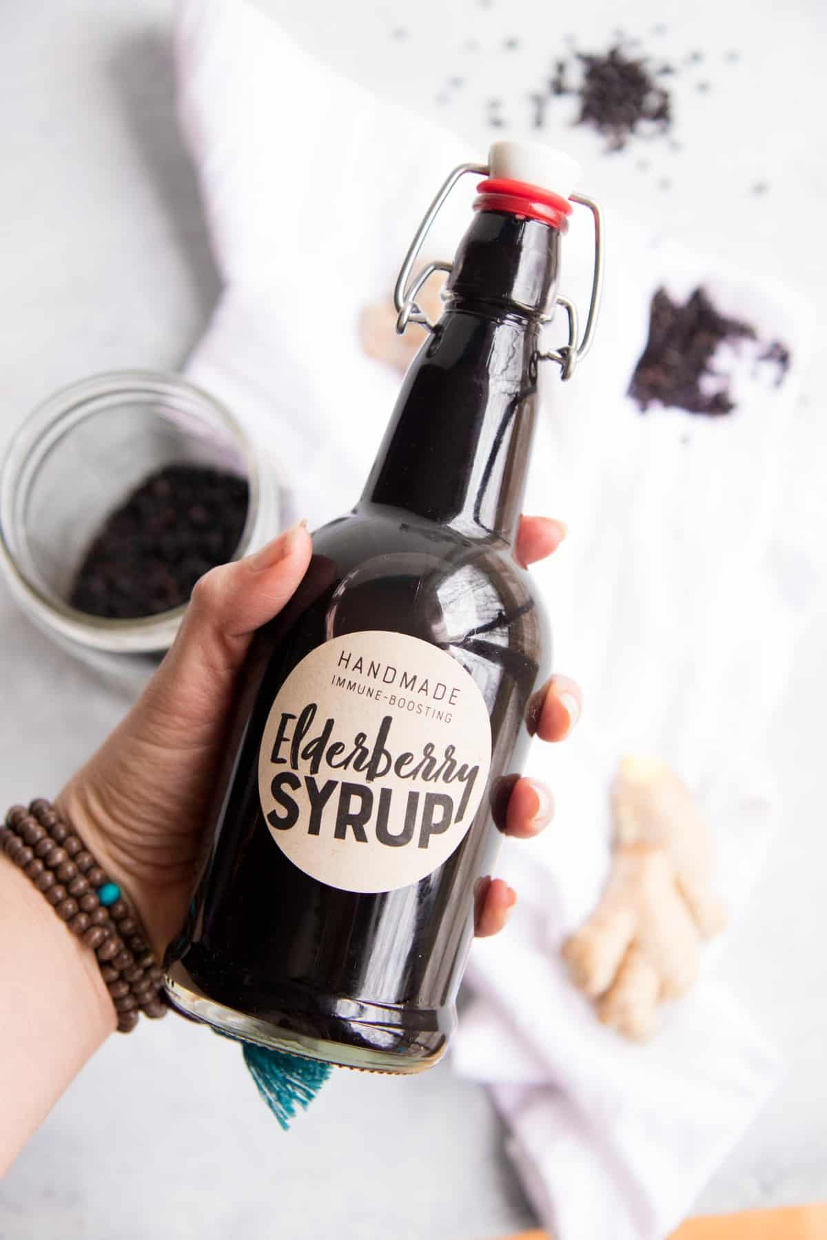 """A hand holds a swing-top bottle labeled """"elderberry syrup"""" over a white dish towel and extra ingredients."""