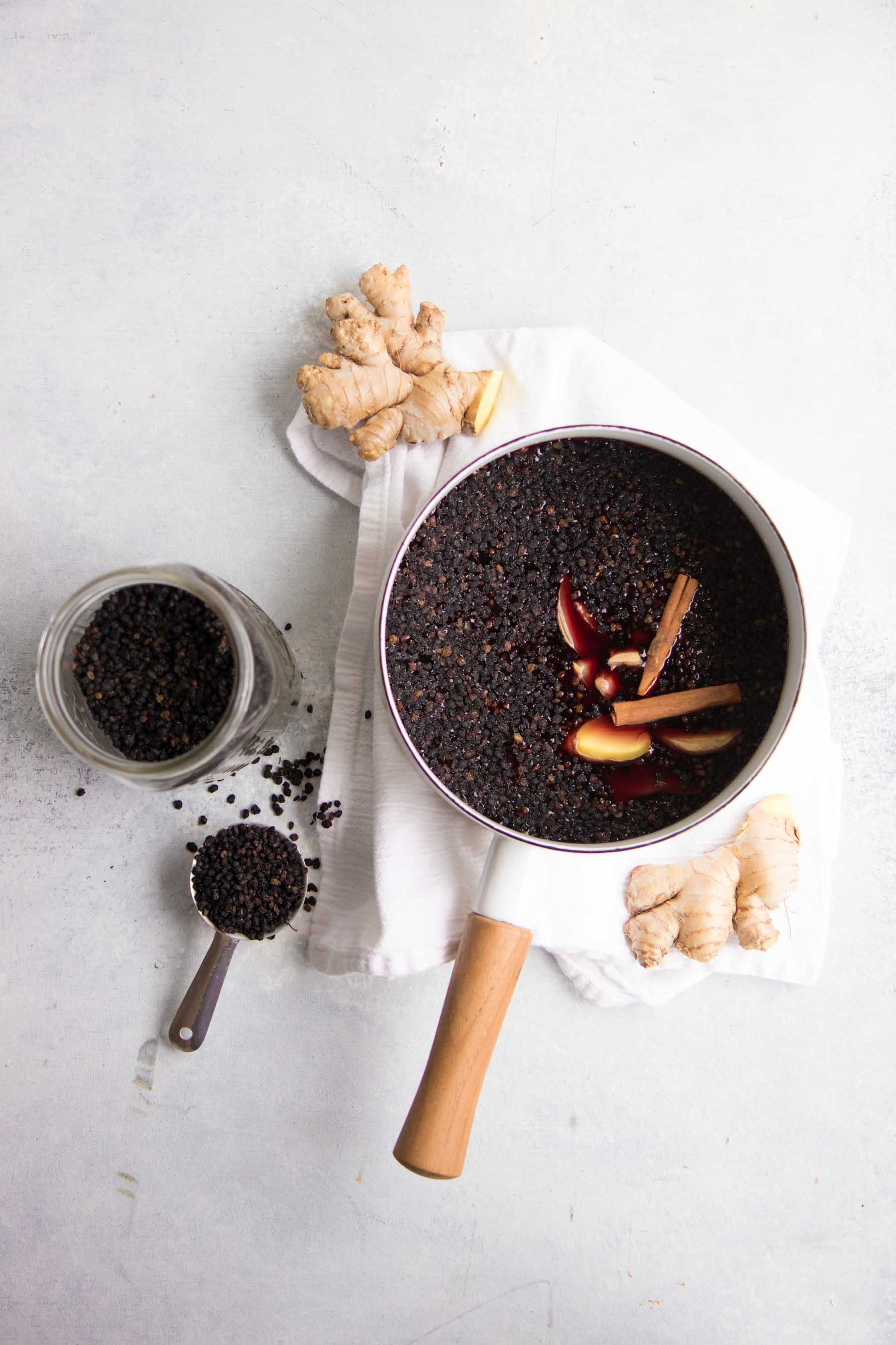 Elderberries sit in a wooden handled pot, surrounded by other ingredients for an elderberry syrup recipe.