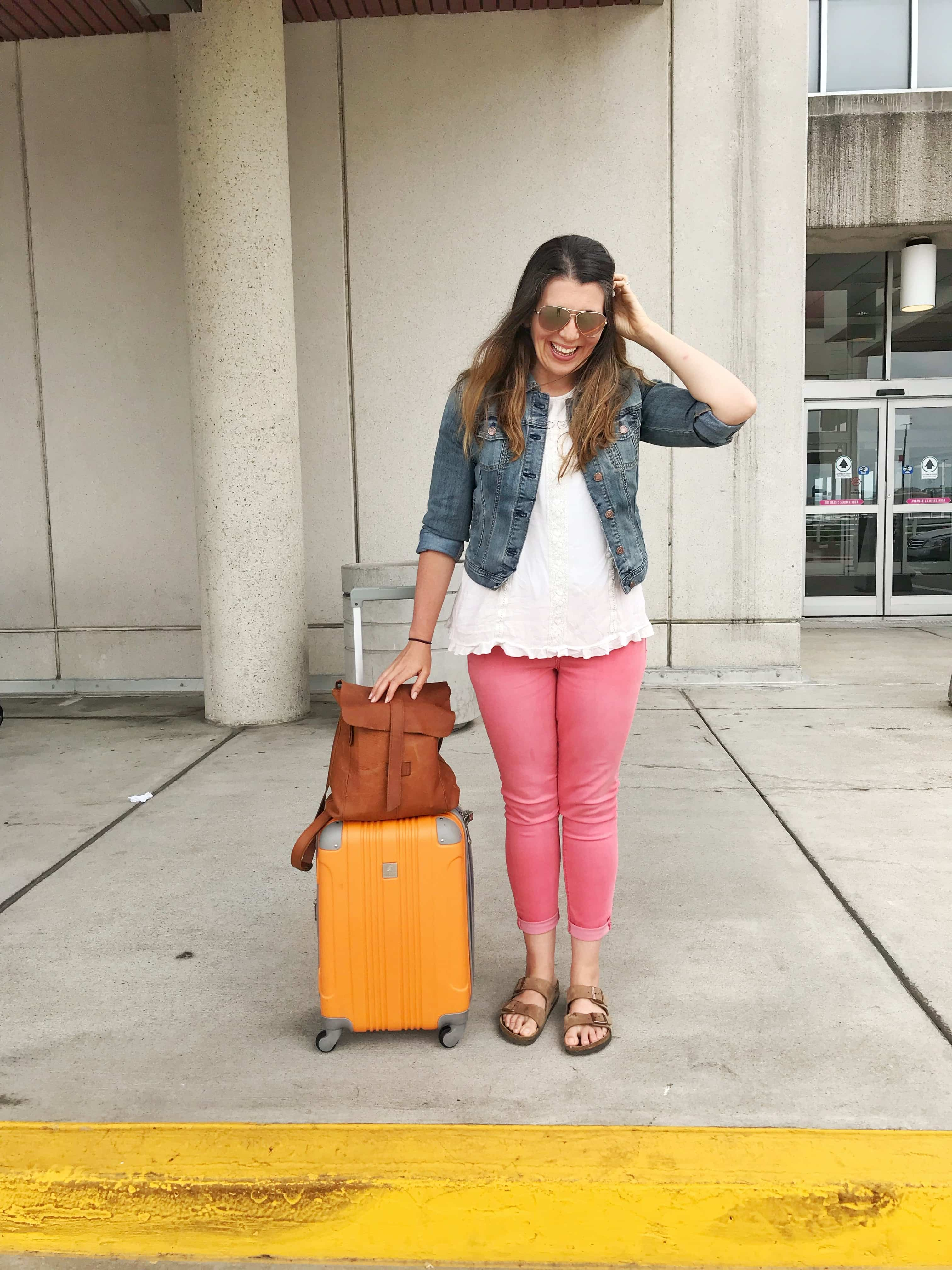 Woman in a denim jacket and pink pants standing next to a rolling suitcase and carry-on bag