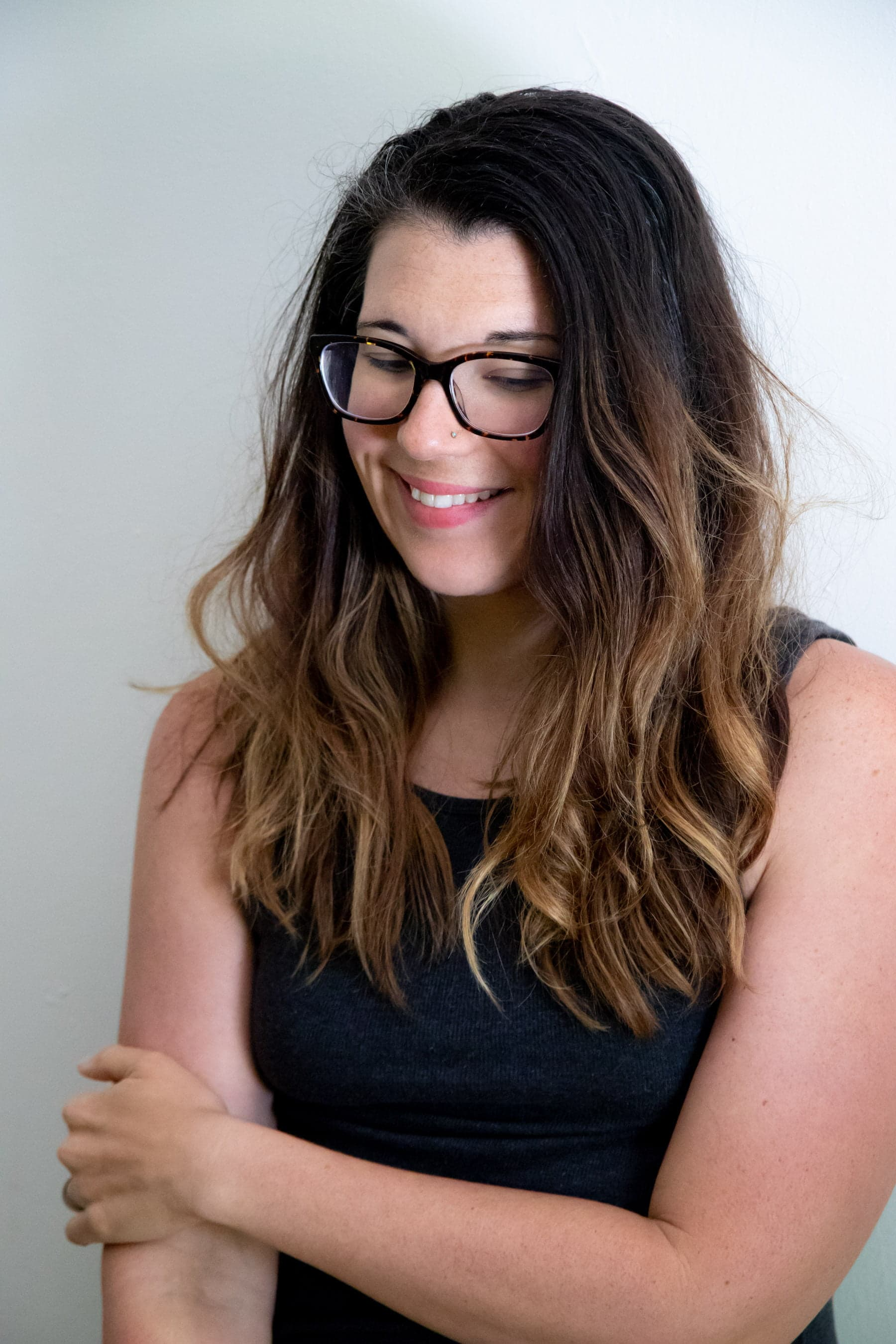 Woman with glasses and long wavy hair, smiling and looking down, with her arms crossed - Lyme disease update