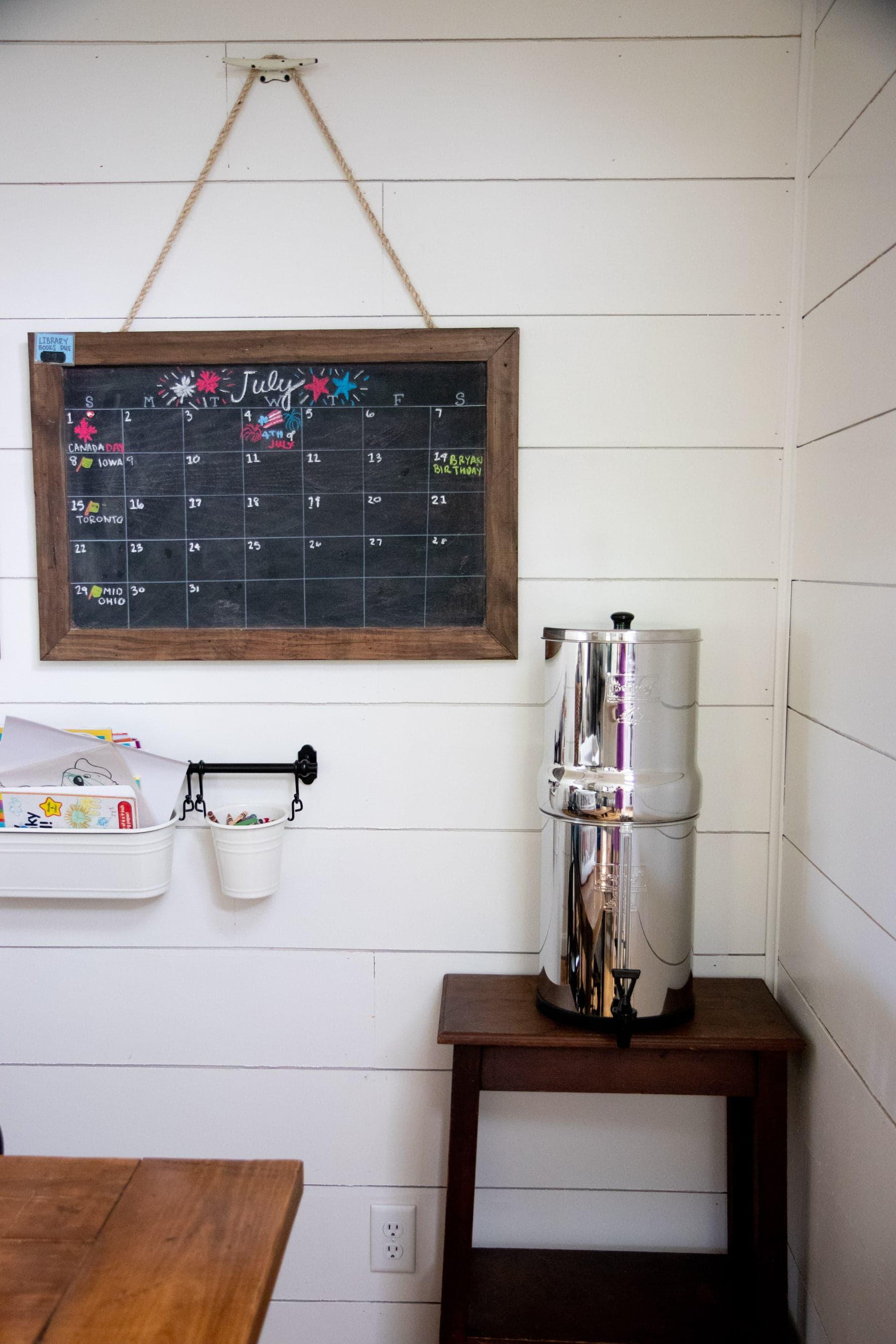 Berkey Water Filter system sitting in a corner near a July chalkboard calendar