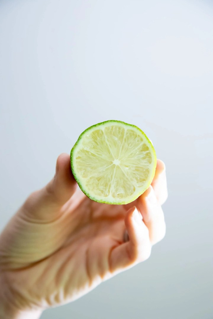 Hand Holding A Halved Lime With The Cut Side Facing Camera