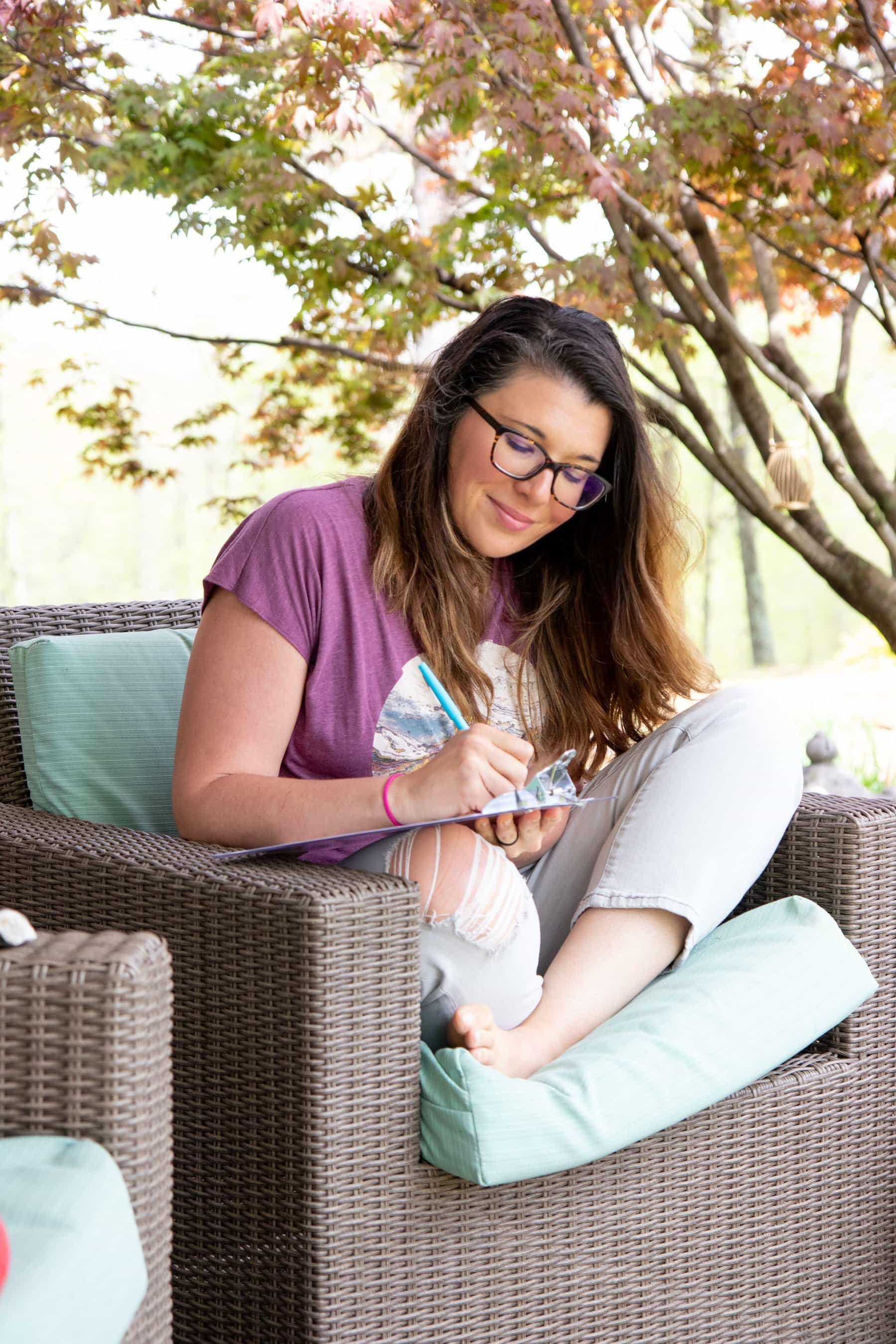 A woman sits outside under a tree on a patio couch crosslegged while writing on a clipboard.