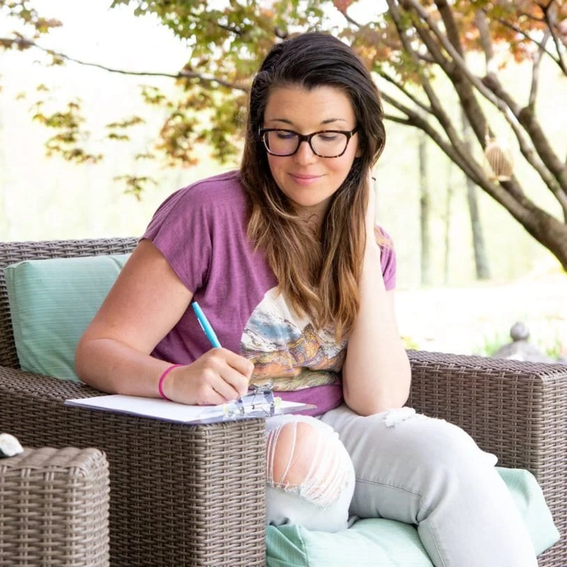 Woman sitting in a chair outside writing during a Worry Time session