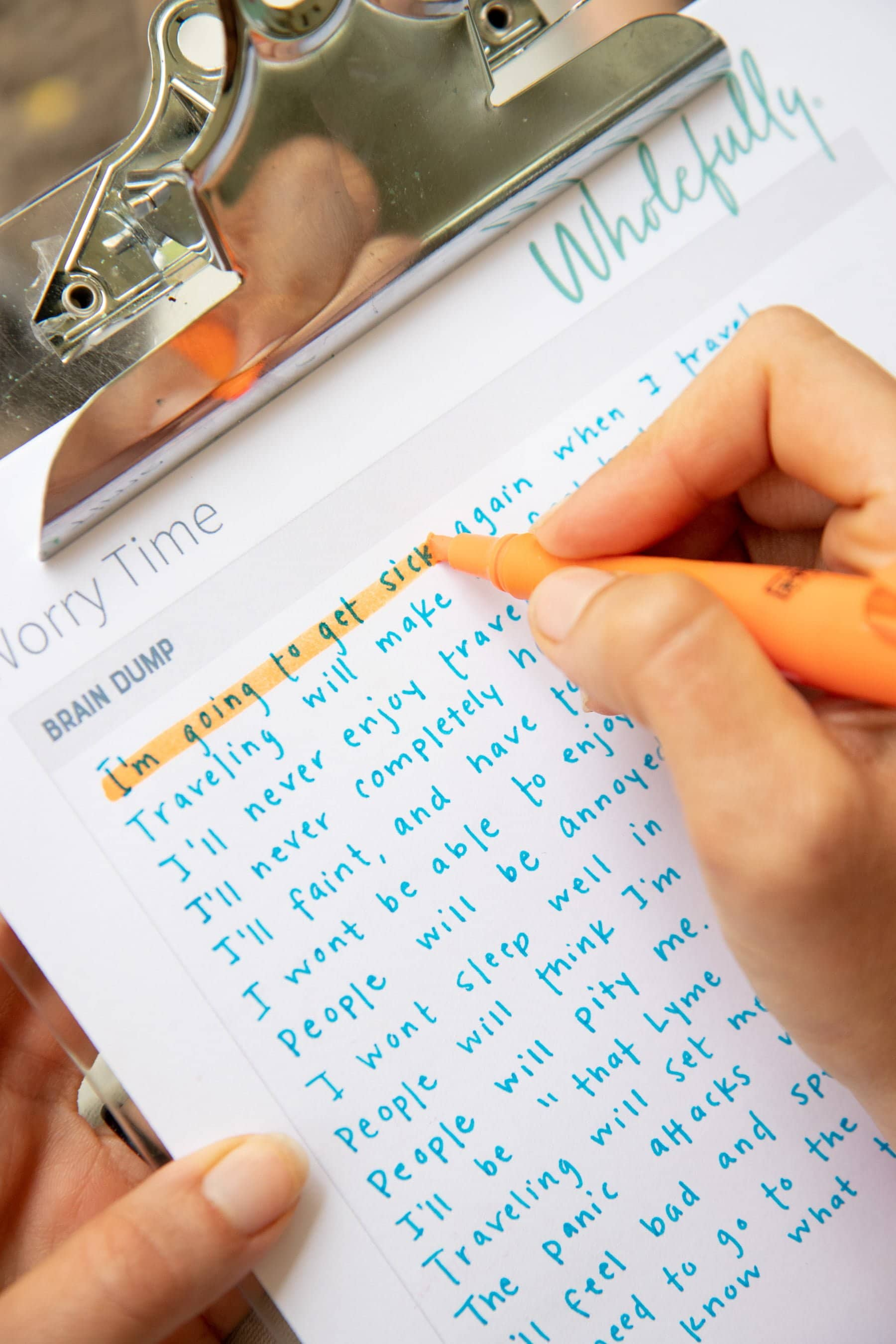 Hands use an orange highlighter to cross off parts of what has been written under the brain dump section of her paper.