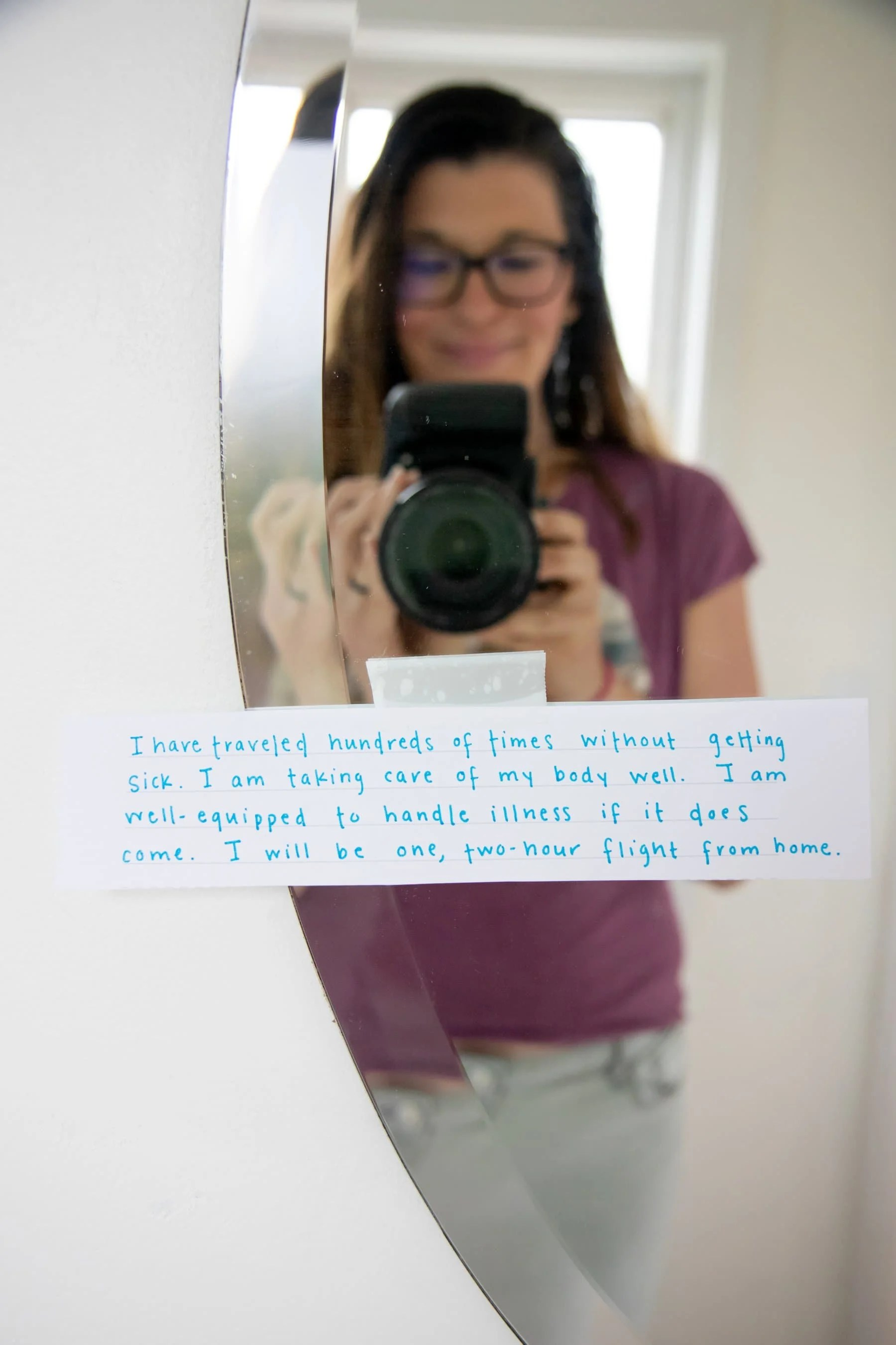 A woman takes a picture of her hand written note that is stuck to the mirror with a piece of tape.