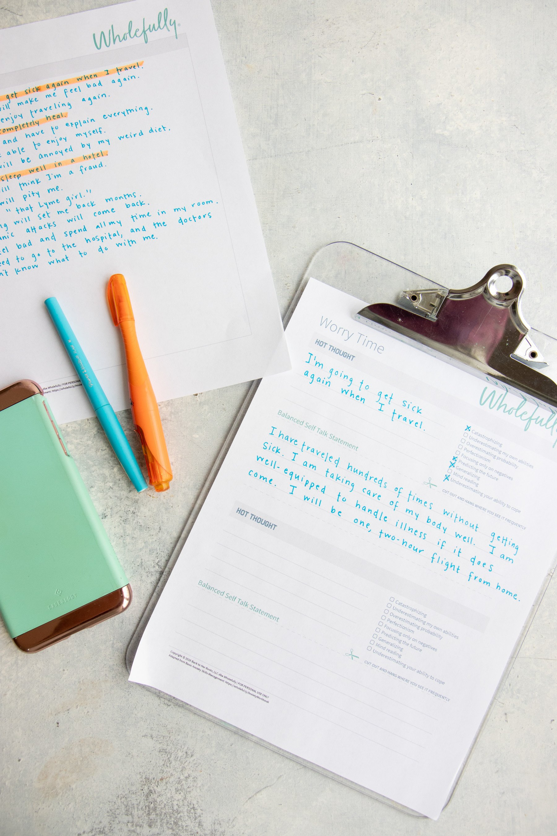 A clipboard holds a Worry Time worksheet with words written on it. A blue and orange highlighter sits on the left hand side, on top of a phone.