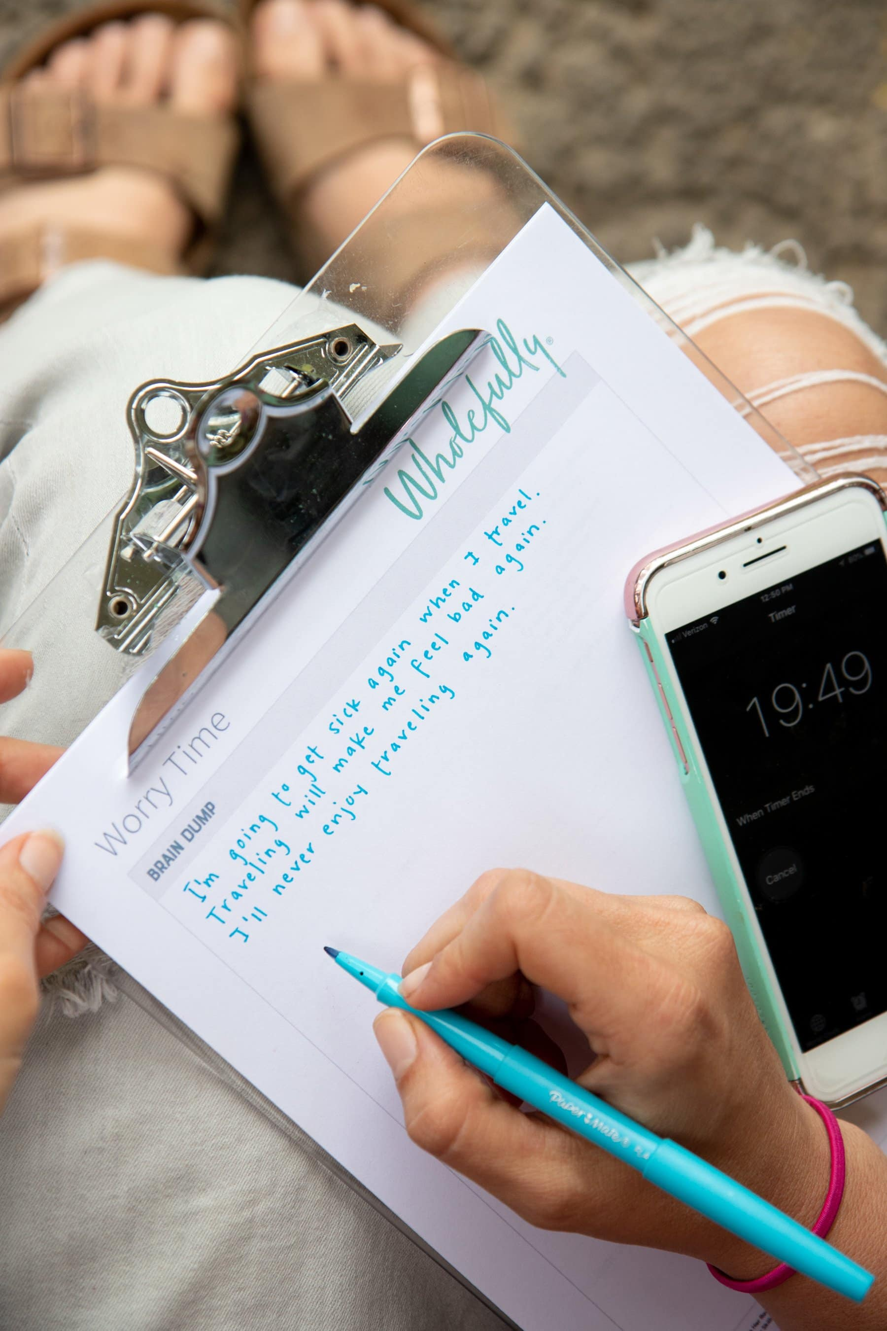 "A girl writes out on her Worry Time worksheet. A phone with a timer set for ""19:49"" is seen on the right hand side."