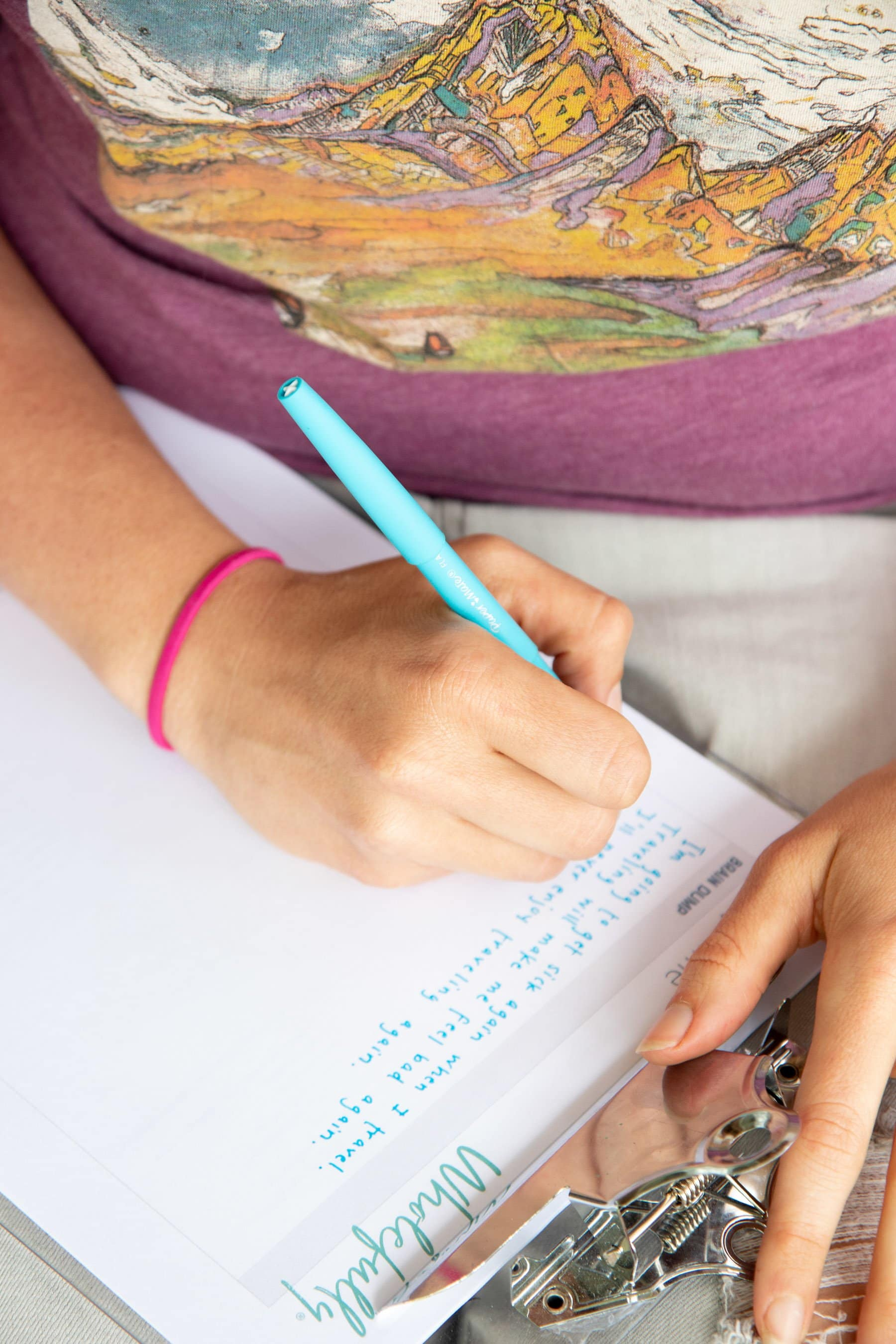 Hand holding a blue pen, writing on a sheet of paper.