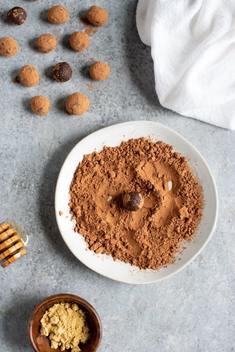 Overhead shot of Ginger Bites (an all-natural upset stomach remedy) being rolled in cocoa powder