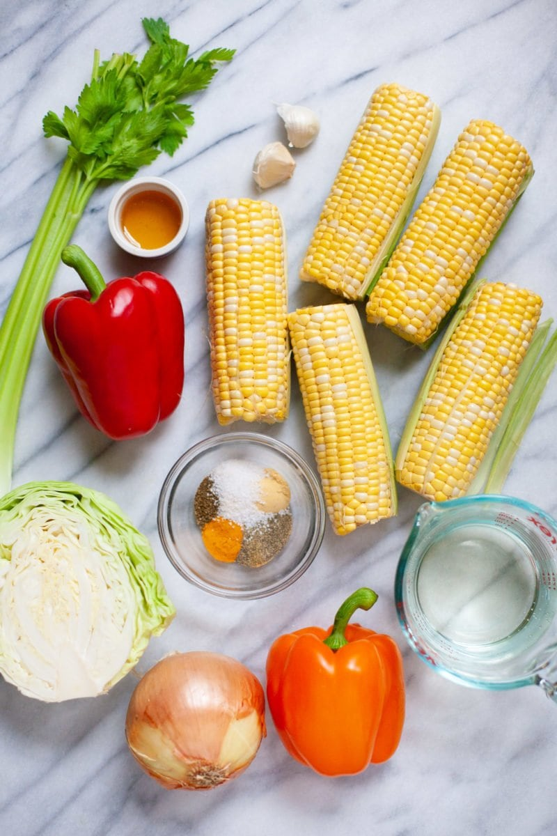 Overhead shot of ingredients for homestyle corn relish - corn, peppers, cabbage, spices