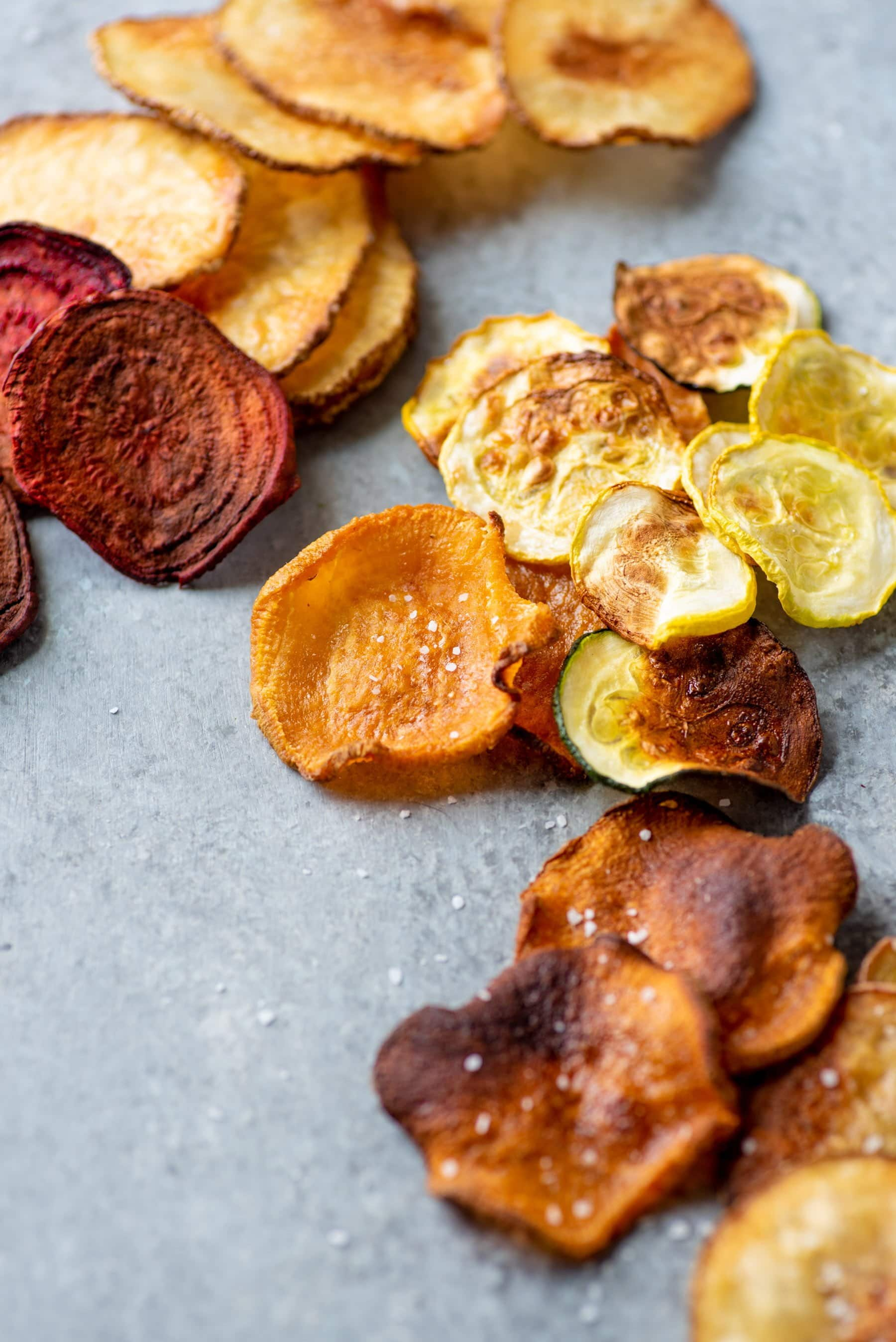 Baked vegetable chips spread out on a grey background