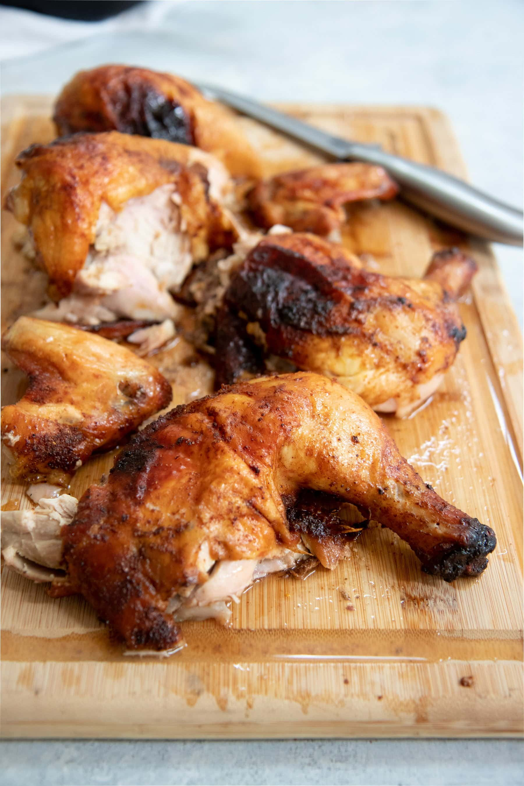 Side angle shot of cut-up grilled chicken on a wooden cutting board