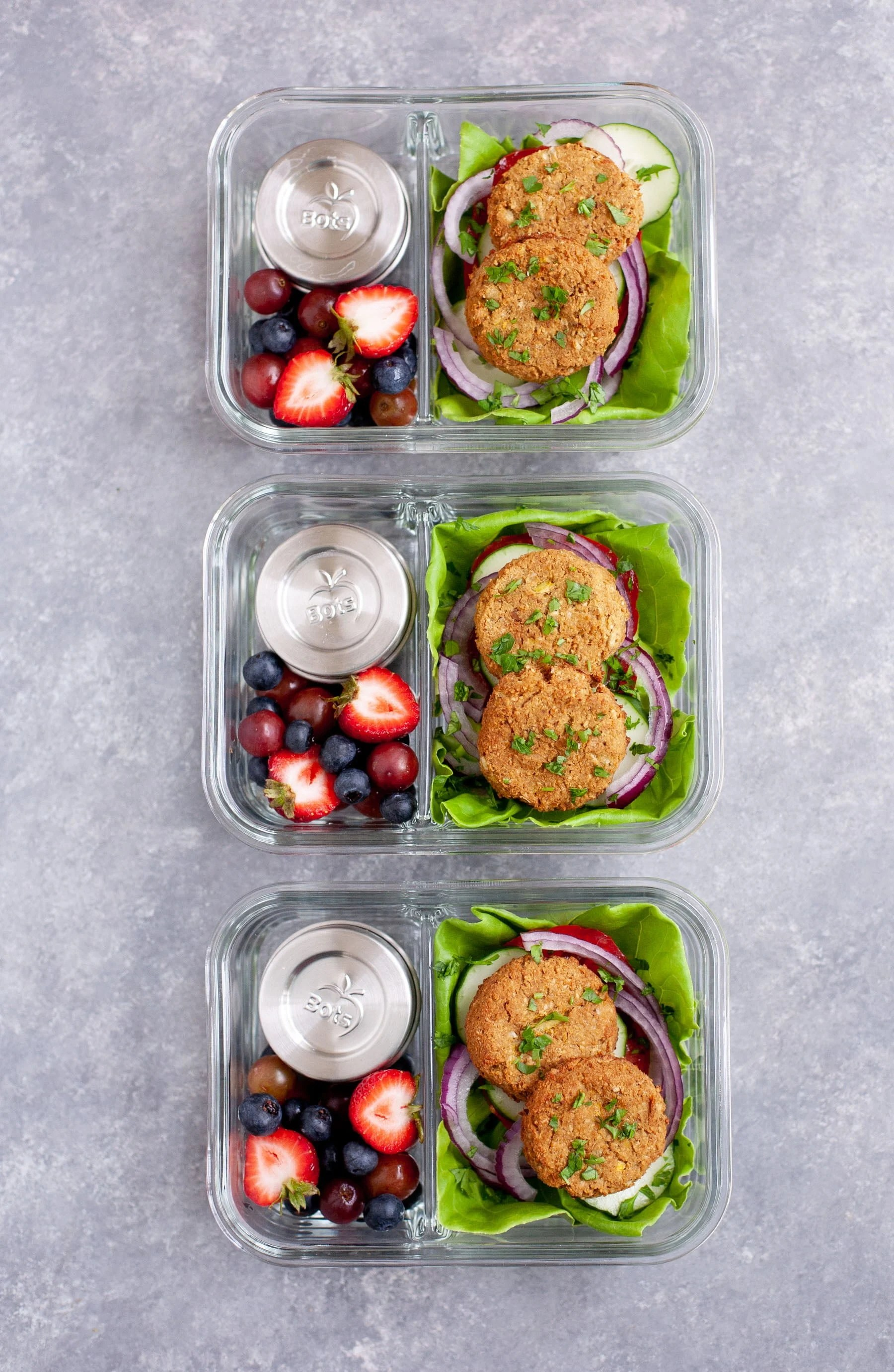 Meal Prep Baked Falafel Lettuce Wraps packed into glass lunch containers with mixed berries and small containers of tahini sauce