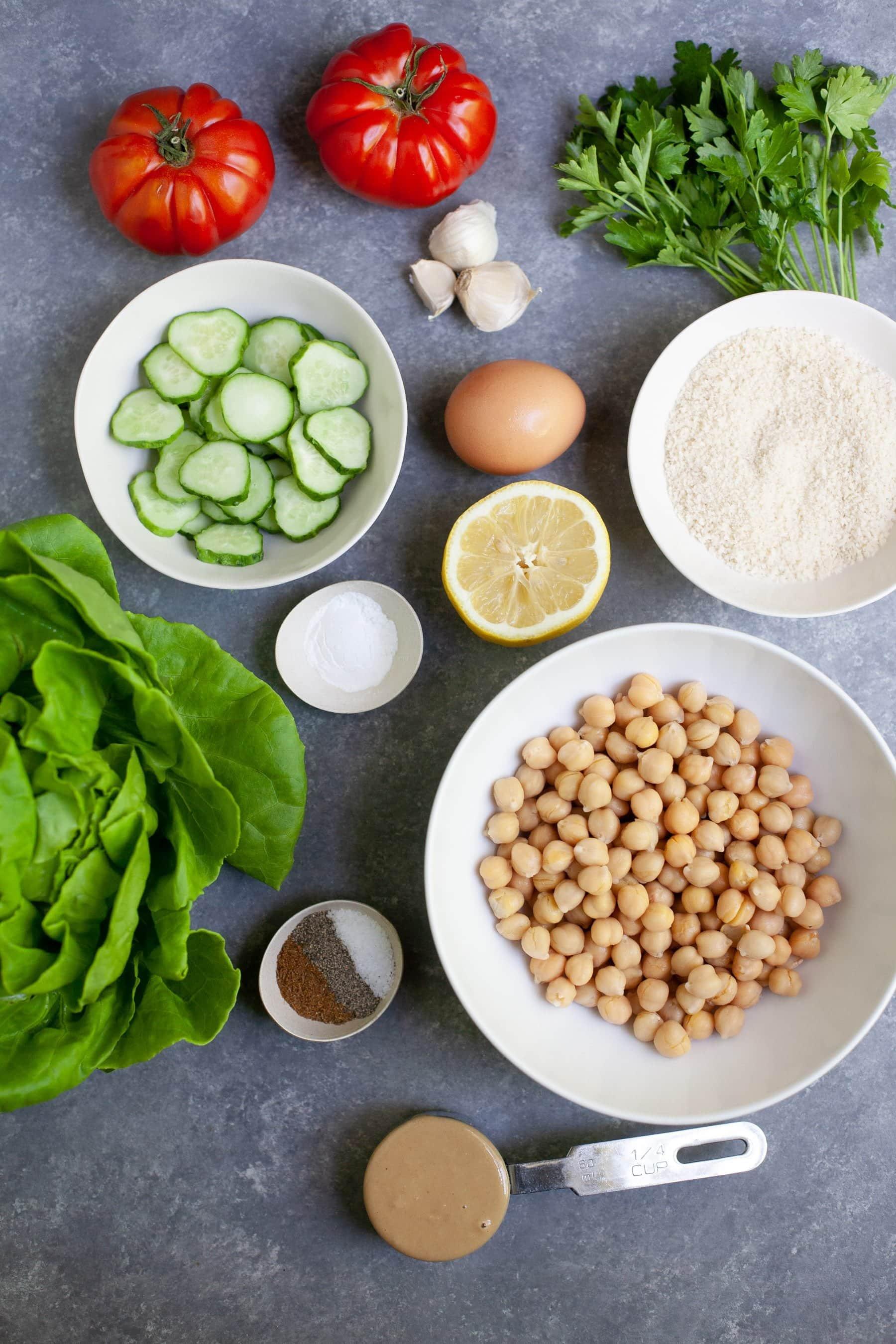 Overhead shot of ingredients for Meal Prep Baked Falafel Lettuce Wraps - chickpeas, lettuce, lemon, cucumber, egg