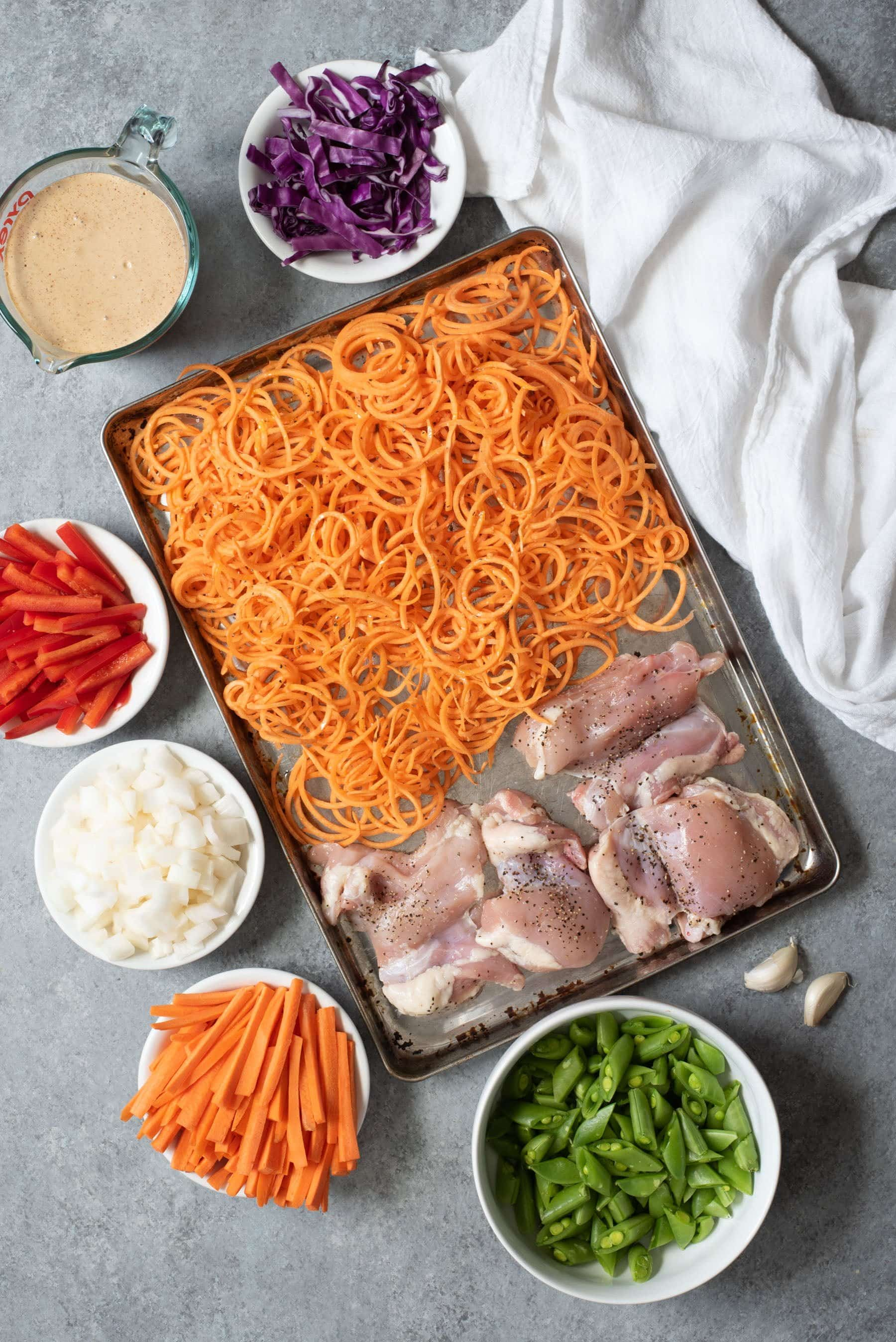 Overhead shot of chicken and sweet potato noodles on a sheet pan, surrounded by small bowls of veggies for Meal Prep Chicken Pad Thai with Sweet Potato Noodles