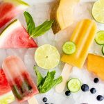 Overhead shot of three flavors of frozen fruit pops arranged on a tray of crushed ice, surrounded by fresh fruit