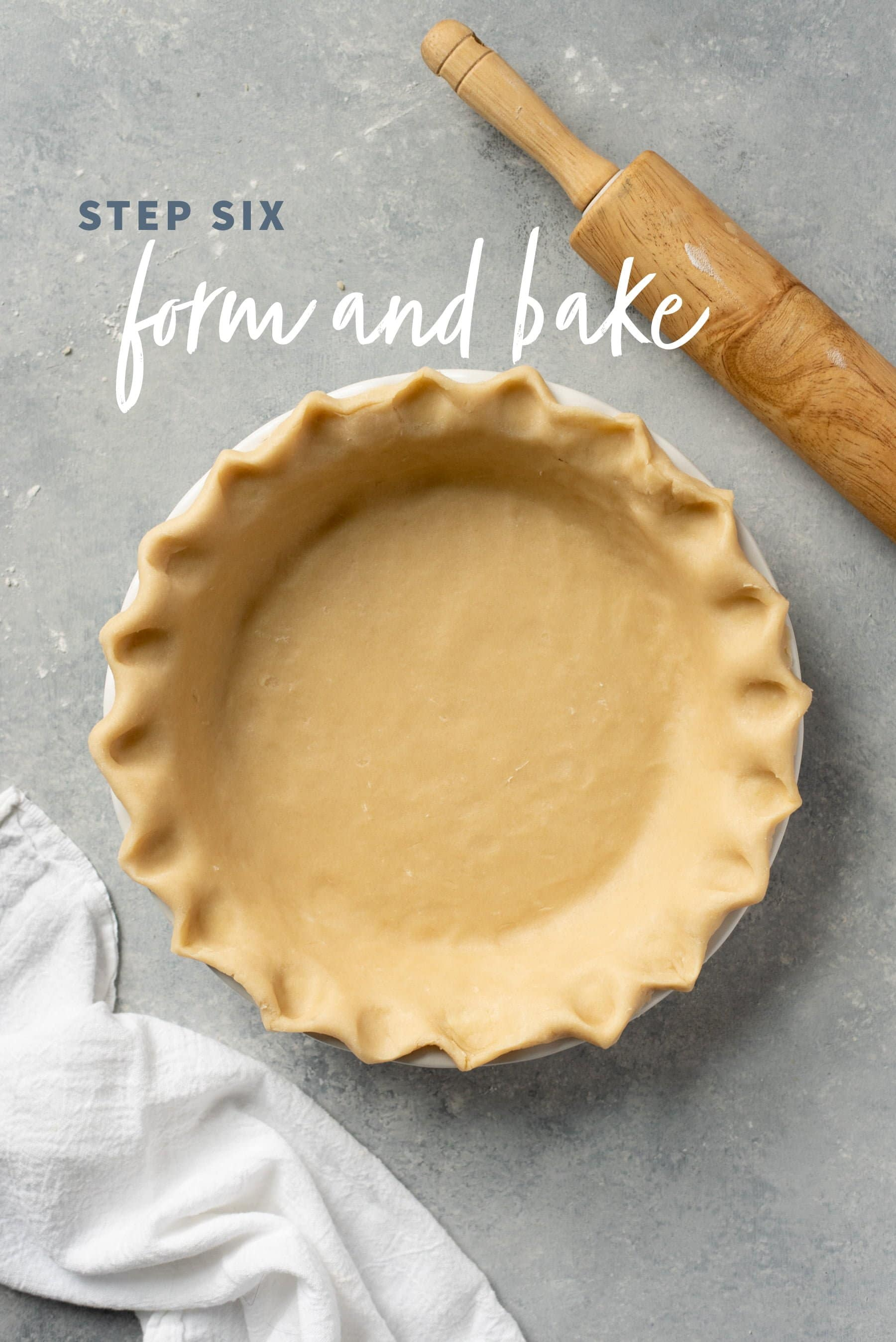 Unbaked pie crust with fluted edges pressed into a pie pan on a gray background