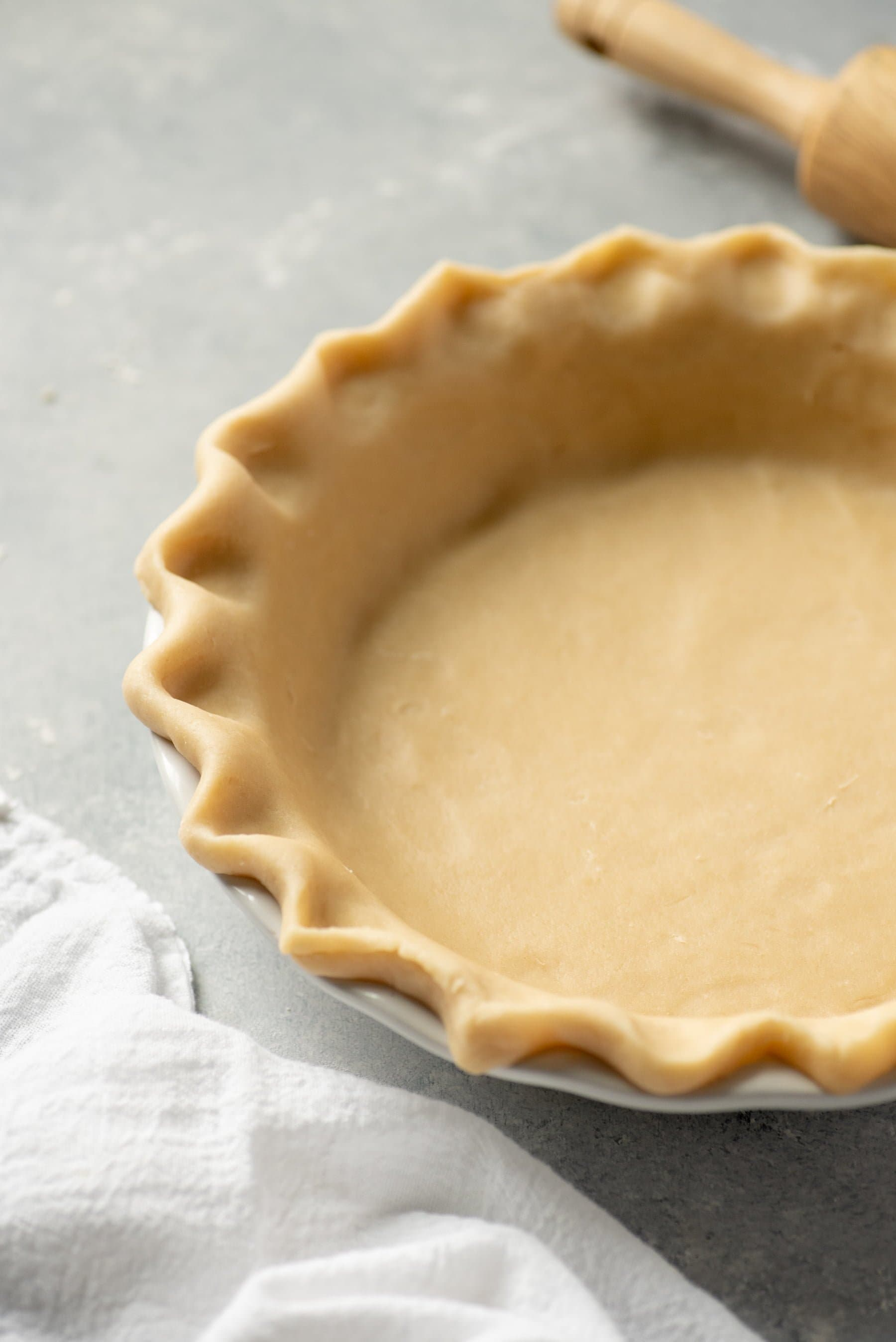 Close-up of unbaked pie crust with fluted edges pressed into a pie pan on a gray background